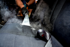 Detailer cleaning the back seat of a car - Interior car detailing near me  in Newcastle NSW
